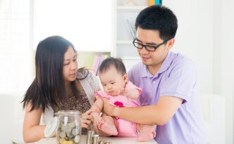 Asian baby putting coins into the glass bottle with help of pare
